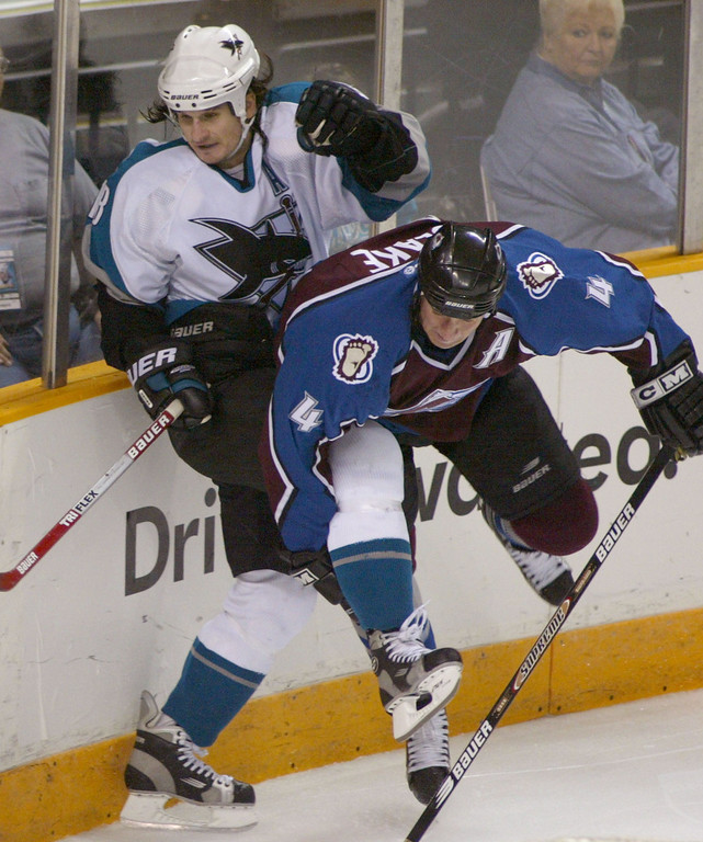 . San Jose Sharks\' Mike Ricci, left, is checked into the boards by Colorado Avalanche\'s Rob Blake during the third period Saturday, Oct. 19, 2002, in San Jose, Calif. The Avalanche won 3-1. (AP Photo/John Todd)