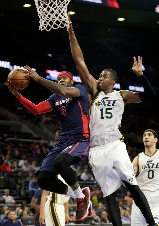 . Detroit Pistons\' Josh Smith (6) goes to the basket against Utah Jazz\'s Derrick Favors (15) during the second half of an NBA basketball game Sunday, Nov. 9, 2014, in Auburn Hills, Mich. The Jazz defeated the Pistons 97-96. (AP Photo/Duane Burleson)