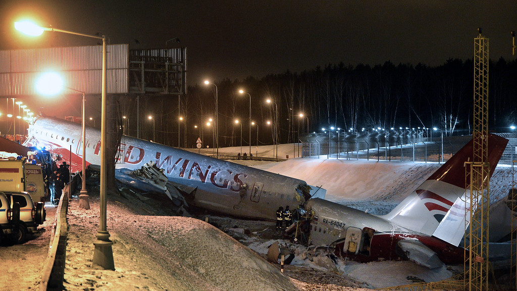 . Russian police investigators and emergency services teams work at the Tu-204 jet crash site near the Vnukovo airport outside Moscow on December 29, 2012. Four people were killed and four were injured when a Russian-made airliner overshot a runway on landing at a Moscow airport and crashed onto a nearby highway, officials said. KIRILL KUDRYAVTSEV/AFP/Getty Images