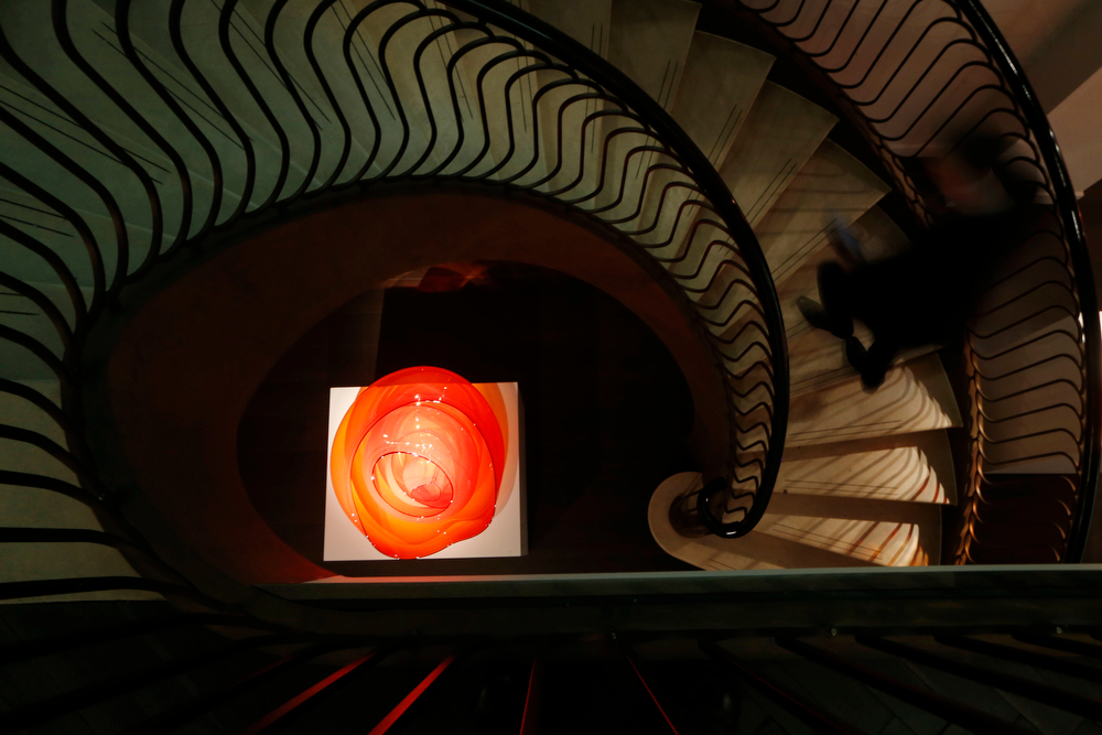 . A man walks up a staircase by a glass sculpture \'Fire Orange Basket Set\' by U.S. artist Dale Chihuly during the launch of an exhibition of his work \'Dale Chihuly: Beyond the Object\' at the Halcyon Gallery in London, Tuesday, Feb. 4, 2014. (AP Photo/Sang Tan)