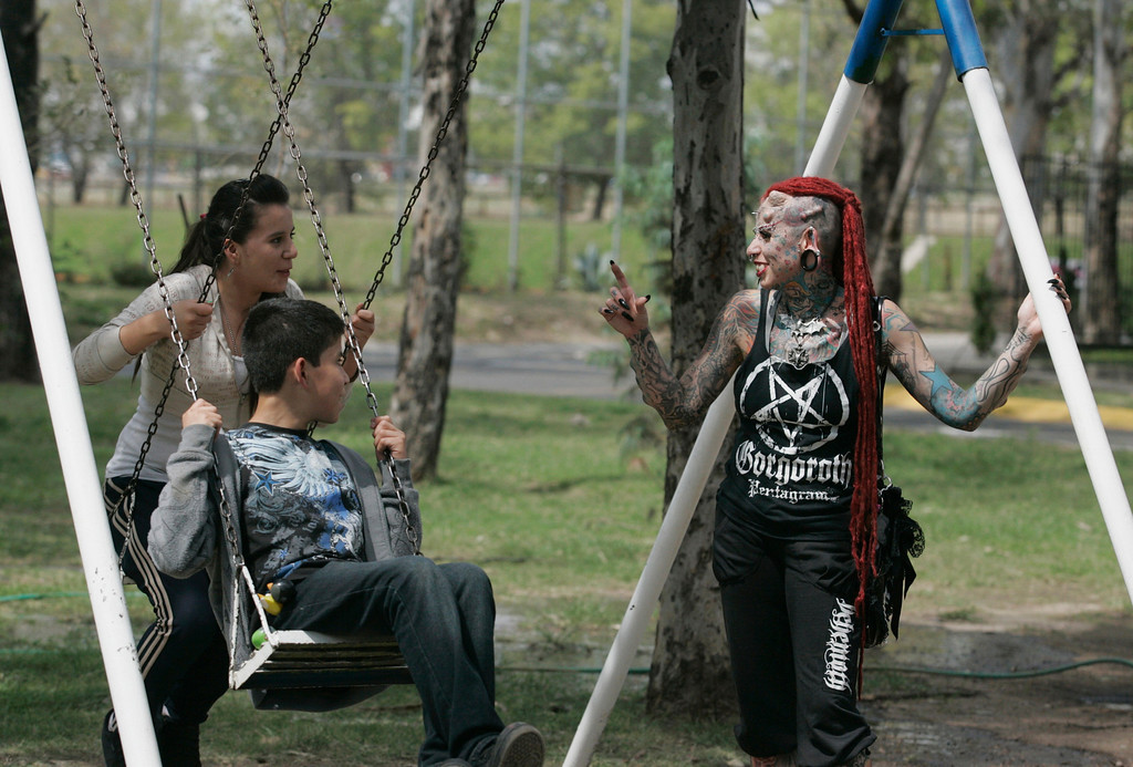 . Maria Jose Cristerna  plays with her children Silvana (rear) and David at a park in Guadalajara February 29, 2012. REUTERS/Alejandro Acosta