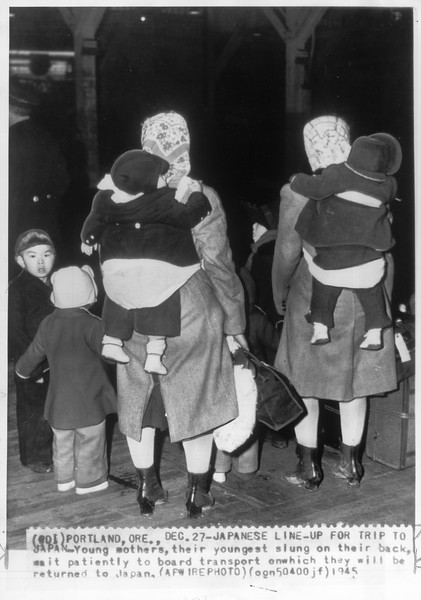 """""""Japanese Line-Up for Trip to Japan -- Young mothers, their youngest slung on their back, wait patiently to board transport on which they will be returned to Japan.""""--caption on photograph"""