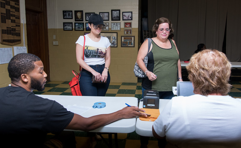 08/14/18  Wesley Bunnell | Staff  Official Checkers Jerome Hardy, L, and Izabella Szczepanski, R, help check in Niomi Figueroa, 2nd L, and Alida Santana-Figueroa at the St. Francis of Assisi Church Hall voting location on Tuesday afternoon.