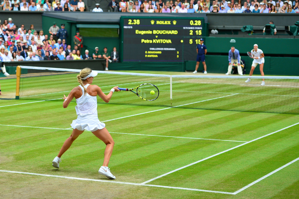 Description of . Canada\'s Eugenie Bouchard returns to Czech Republic\'s Petra Kvitova during their women\'s singles final match on day twelve of  the 2014 Wimbledon Championships at The All England Tennis Club in Wimbledon, southwest London, on July 5, 2014. Kvitova stormed to her second Wimbledon title in the shortest women\'s final since 1983 as the Czech sixth seed crushed Canada\'s Eugenie Bouchard 6-3, 6-0. (CARL COURT/AFP/Getty Images)