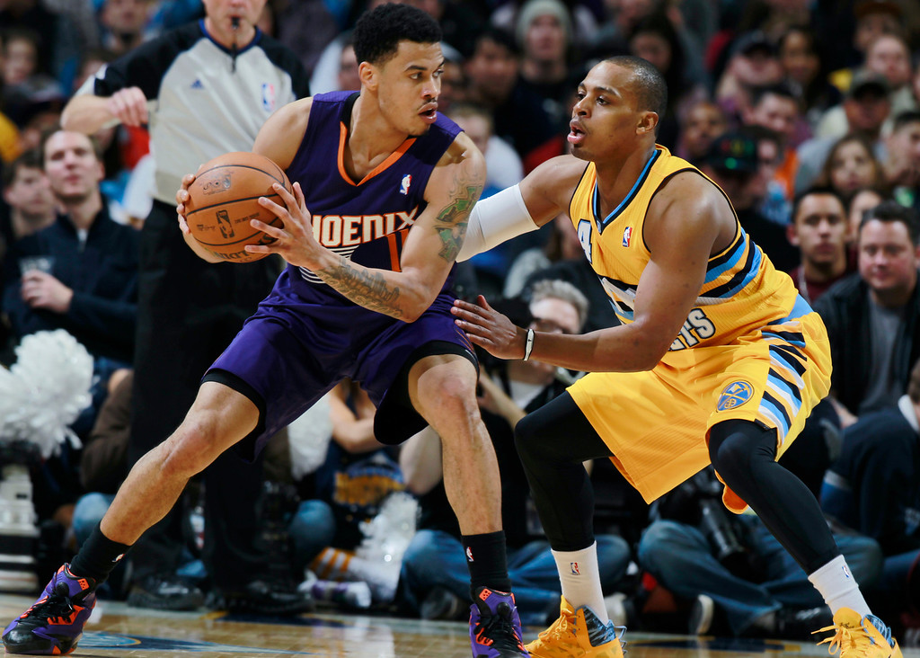 . Phoenix Suns guard Gerald Green, left, looks to pass the ball as Denver Nuggets guard Randy Foye covers in the fourth quarter of the Suns\' 103-99 victory in an NBA basketball game in Denver on Friday, Dec. 20, 2013. (AP Photo/David Zalubowski)