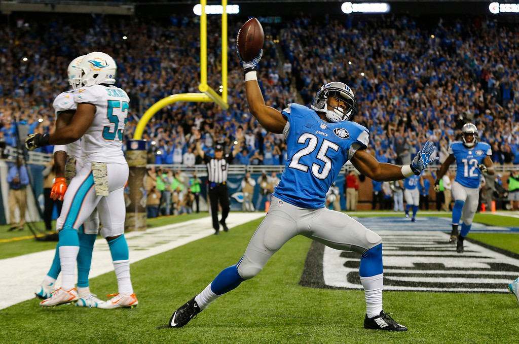 . Detroit Lions running back Theo Riddick (25) celebrates a touchdown during the second half of an NFL football game against the Miami Dolphins in Detroit, Sunday, Nov. 9, 2014. (AP Photo/Paul Sancya)