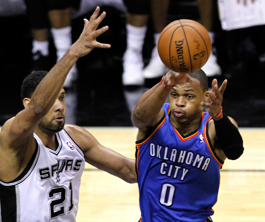 . Russell Westbrook #0 of the Oklahoma City Thunder passes the ball while guarded by Tim Duncan #21 of the San Antonio Spurs in the third quarter in Game One of the Western Conference Finals during the 2014 NBA Playoffs at AT&T Center on May 19, 2014 in San Antonio, Texas.  (Photo by Chris Covatta/Getty Images)