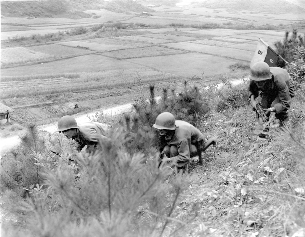 . 1950: The American fighting-man, representing U.S. troops involved in the Korean War. American soldiers of the Eighth Cavalry Regiment crouch through a low brush on a Korean hilltop North of the 38th parallel after planting their guidon within sight of the Communist forces on nearby hills on Oct. 15, 1950 during the Korean War. The road in the background runs directly north to the North Korean capital of Pyongyang. (AP Photo/Max Desfor)