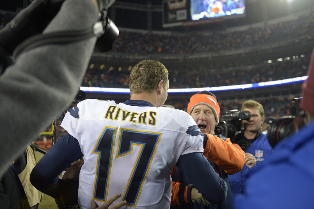 . Denver Broncos head coach John Fox and San Diego Chargers quarterback Philip Rivers (17) shake hands after the game.The  Broncos lost to the Chargers 27 -20.  The Denver Broncos vs. the San Diego Chargers at Sports Authority Field at Mile High in Denver on December 12, 2013. (Photo by Joe Amon/The Denver Post)