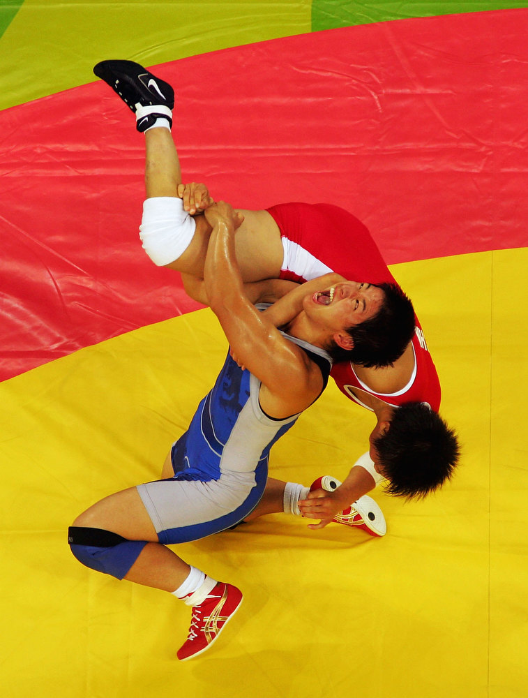 Description of . Kyoko Hamaguchi (blue) of Japan flips Xu Wang of China during the women's Freestyle wrestling 72 kg Semi Final round on August 23, 2004 during the Athens 2004 Summer Olympic Games at Ano Liossia Olympic Hall in Athens, Greece. (Photo by Al Bello/Getty Images)