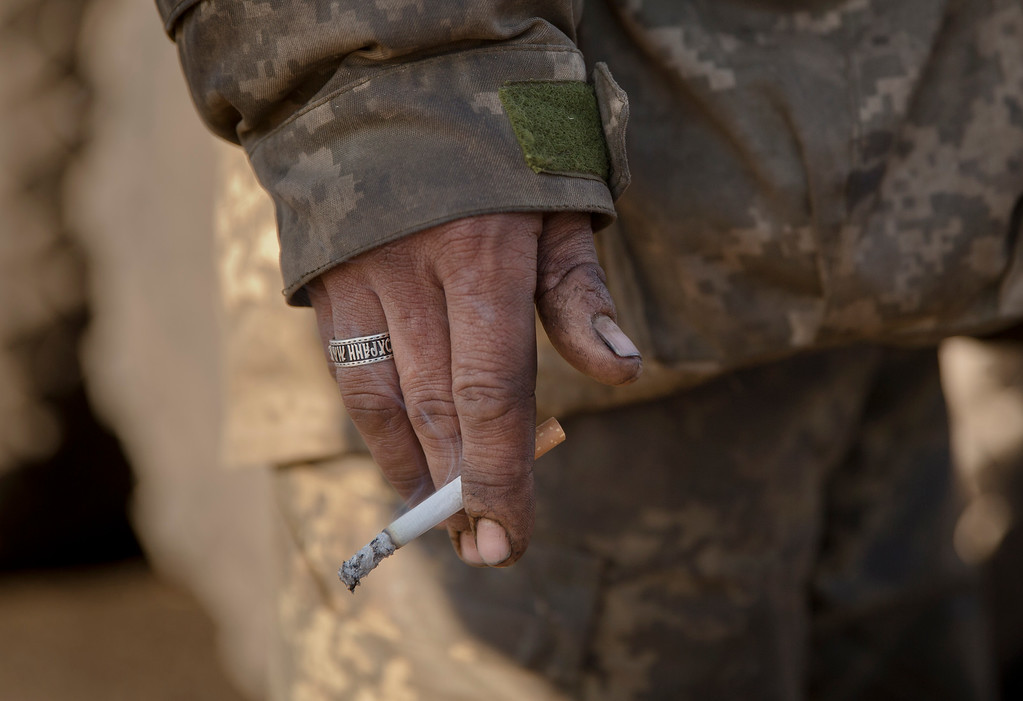""". A Ukrainian serviceman wearing a ring engraved with a fragment of an Orthodox prayer that reads \""""save and protect me\"""" stands outside Artemivsk, Ukraine, after pulling out of Debaltseve, Wednesday, Feb. 18, 2015. After weeks of relentless fighting, the embattled Ukrainian rail hub of Debaltseve fell Wednesday to Russia-backed separatists, who hoisted a flag in triumph over the town. The Ukrainian president confirmed that he had ordered troops to pull out and the rebels reported taking hundreds of soldiers captive. (AP Photo/Vadim Ghirda)"""