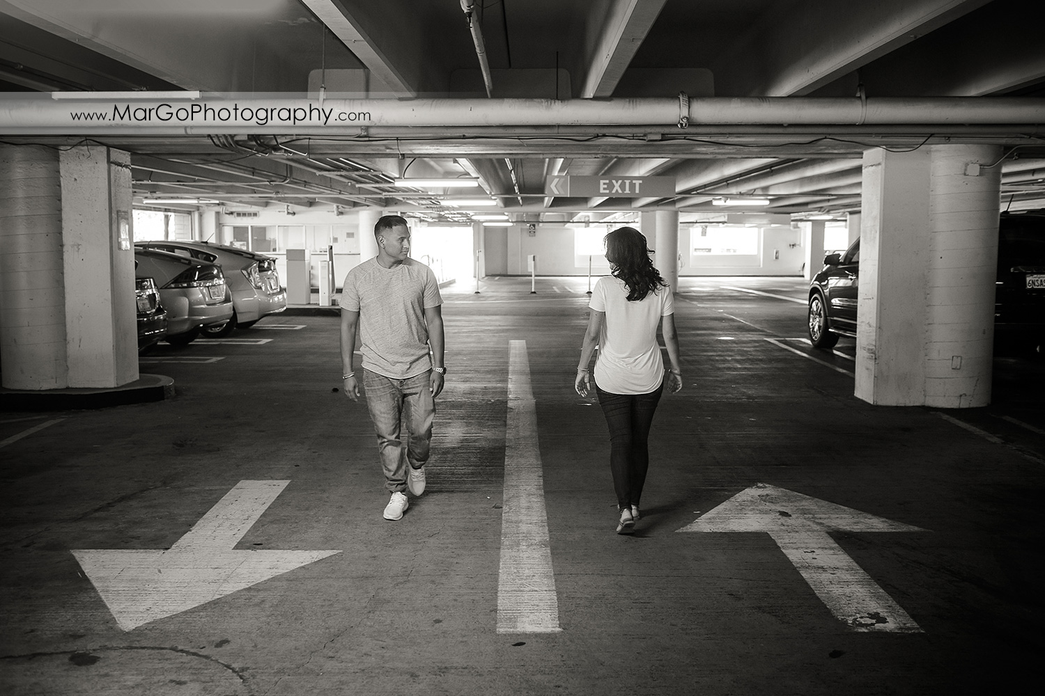 black and white photo of man and woman walking opossit direction with white arrows on the ground during engagement session in San Pedro Square Market garage in San Jose