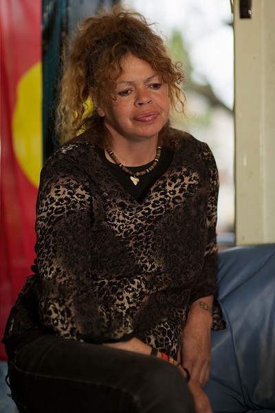 Indigenous Australian Woman seated in front of Aboriginal Flag