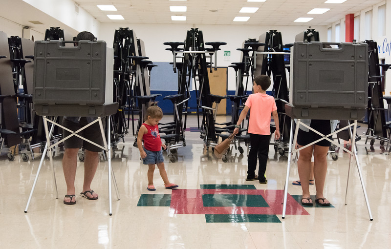 08/14/18  Wesley Bunnell | Staff  Derrick Williams, L, and wife Darci Williams, R, vote at Slade Middle School voting station on Tuesday evening as their children Alan, age 2, and Titus, age 8, wait.