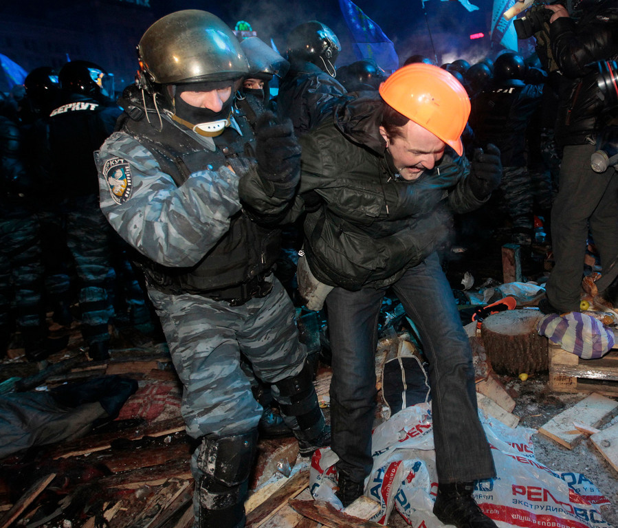 . A Ukrainian riot policeman pulls a Pro-European Union activist out from a tent on the Independence Square in Kiev, Ukraine, Wednesday, Dec. 11, 2013. Security forces clashed with protesters as they began tearing down opposition barricades and tents set up in the center of the Ukrainian capital early Wednesday, in an escalation of the weeks-long standoff threatening the leadership of President Viktor Yanukovych. (AP Photo/Sergei Chuzavkov)