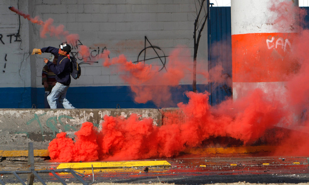 """. A protestor opposed to newly sworn-in Mexican President Enrique Pena Nieto throws an unidentified object towards the National Congress, just hours before Pena Nieto was to formally take the oath of office in Mexico City, Saturday, Dec. 1, 2012.  Hundreds of protesters banged on the steel security barriers around Congress, threw rocks, bottle rockets and firecrackers at police and yelled \""""Mexico without PRI!\""""  Pena Nieto took power at midnight in a symbolic ceremony and formally took the oath of office Saturday morning. (AP Photo/Marco Ugarte)"""
