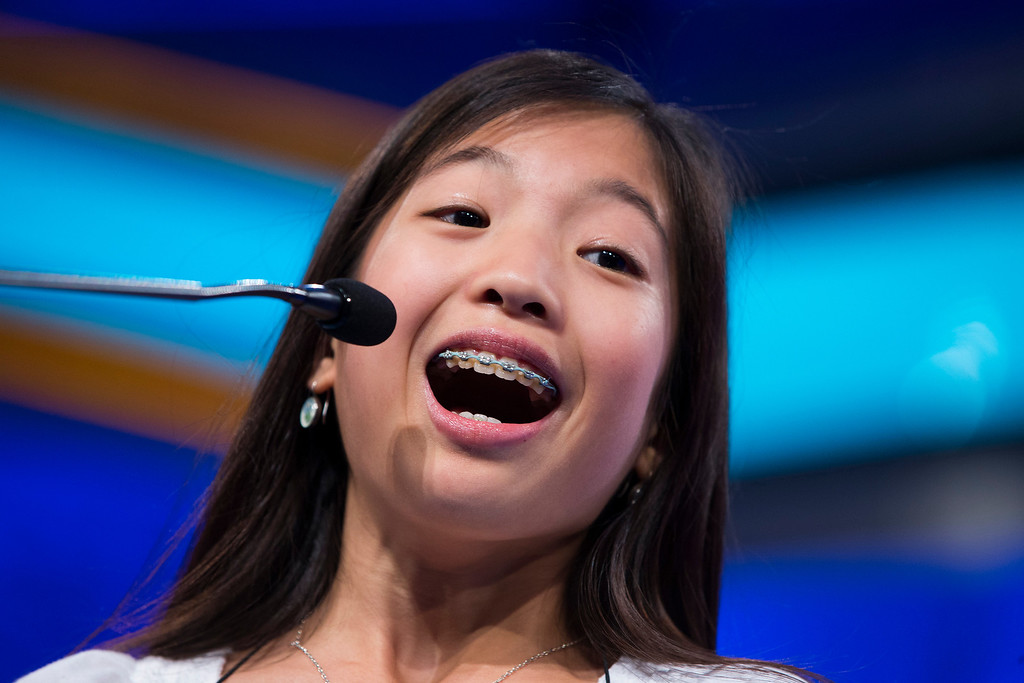 ". Alia Abiad, 14, of Western Springs, Ill., smiles after spelling ""bu�uelo\"" during the final round of the National Spelling Bee, on Thursday, May 29, 2014, in Oxon Hill, Md. (AP Photo/Evan Vucci)"