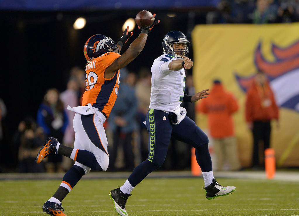 . Seattle Seahawks quarterback Russell Wilson (3) throws a shuttle paddduring the first quarter as Denver Broncos outside linebacker Danny Trevathan (59) chases him down. The Denver Broncos vs the Seattle Seahawks in Super Bowl XLVIII at MetLife Stadium in East Rutherford, New Jersey Sunday, February 2, 2014. (Photo by Joe Amon/The Denver Post)