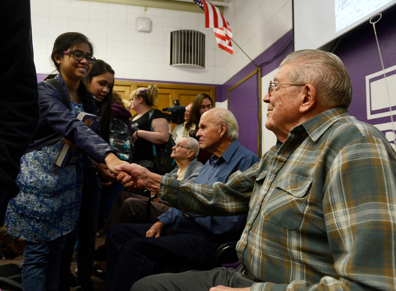 . South High School student, Tuba Jaherun, 15, left, greets WWII U.S. Army Veteran, Earl Lammers, right, Wednesday morning, February 12, 2014 at South High School. Three WWII veterans from the Clermont Park Retirement Community visited Cristina Chacon\'s U.S History class at South High to tell their stories and answer questions from the students. (Photo By Andy Cross / The Denver Post)