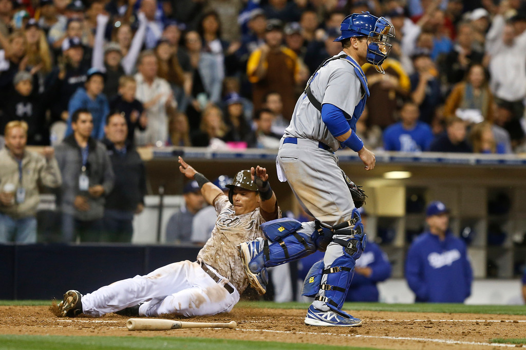 . San Diego Padres\' Everth Cabrera slides past Los Angeles Dodgers catcher A.J. Elliswhile scoring in the eighth inning of the opening game of Major League baseball in the United States Sunday, March 30, 2014, in San Diego.  The Padres won the game 3-1 with a three run eighth inning.  (AP Photo/Lenny Ignelzi)