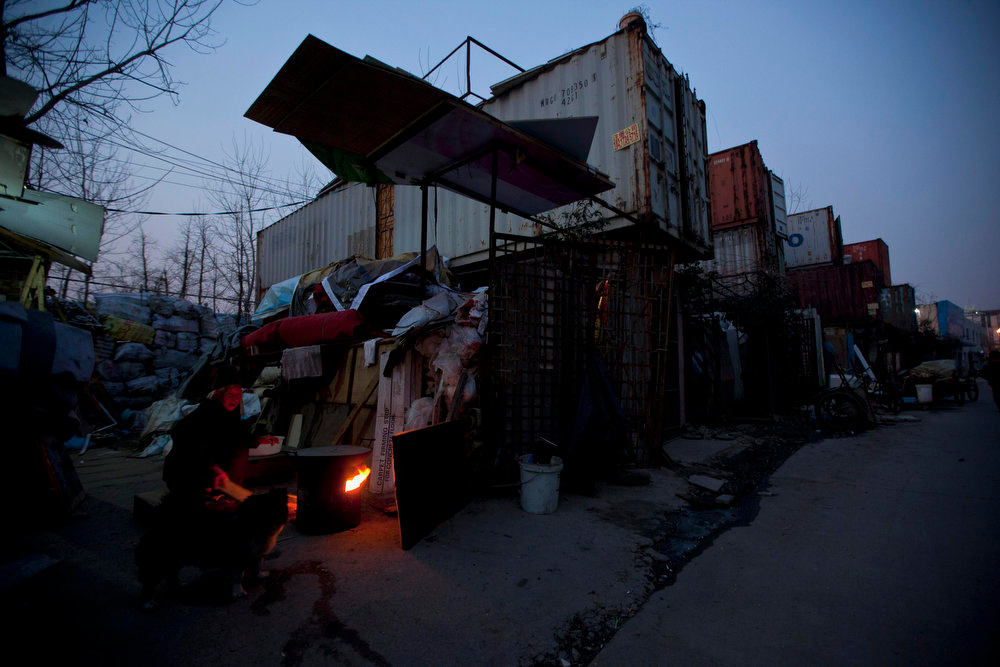 . A woman cooks outside shipping containers which serve as her accommodation, in Shanghai March 4, 2013. The containers, which house different families, were set up by the landlord, who charges a rent of 500 yuan ($80) per month for each container. REUTERS/Aly Song