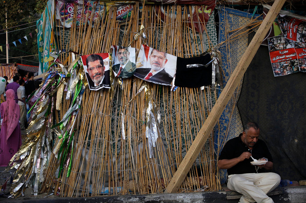 ". A supporter of Egypt\'s ousted President Mohammed Morsi eats under his posters at Nahda Square, where protesters have installed their camp near Cairo University in Giza, southwest of Cairo, Egypt, Saturday, Aug. 10, 2013. The Arabic reads, ""Yes for legitimacy.\"" (AP Photo/Amr Nabil)"