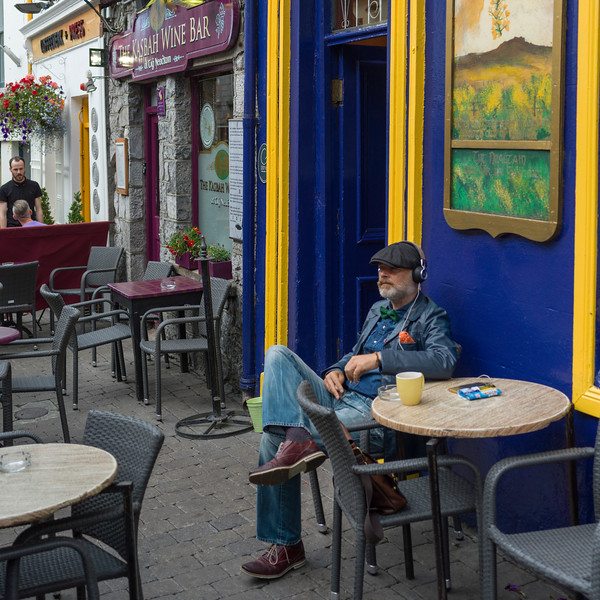 Man listening to music sitting outside the cafe, Galway City, County Galway, Ireland