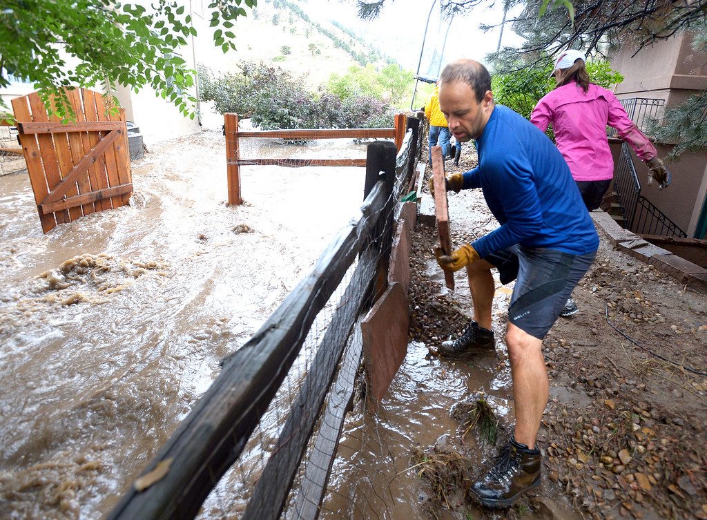 . Jim Thomas uses patio stones to hold back the water from  their home in Boulder, Colo,,  on Friday Sept. 13, 2013.   People in Boulder were ordered to evacuate as water rose to dangerous levels amid a storm system that has been dropping rain for a week. Rescuers struggled to reach dozens of people cut off by flooding in mountain communities, while residents in the Denver area and other areas were warned to stay off flooded streets. (AP Photo/The Daily Camera, Paul Aiken) NO SALES