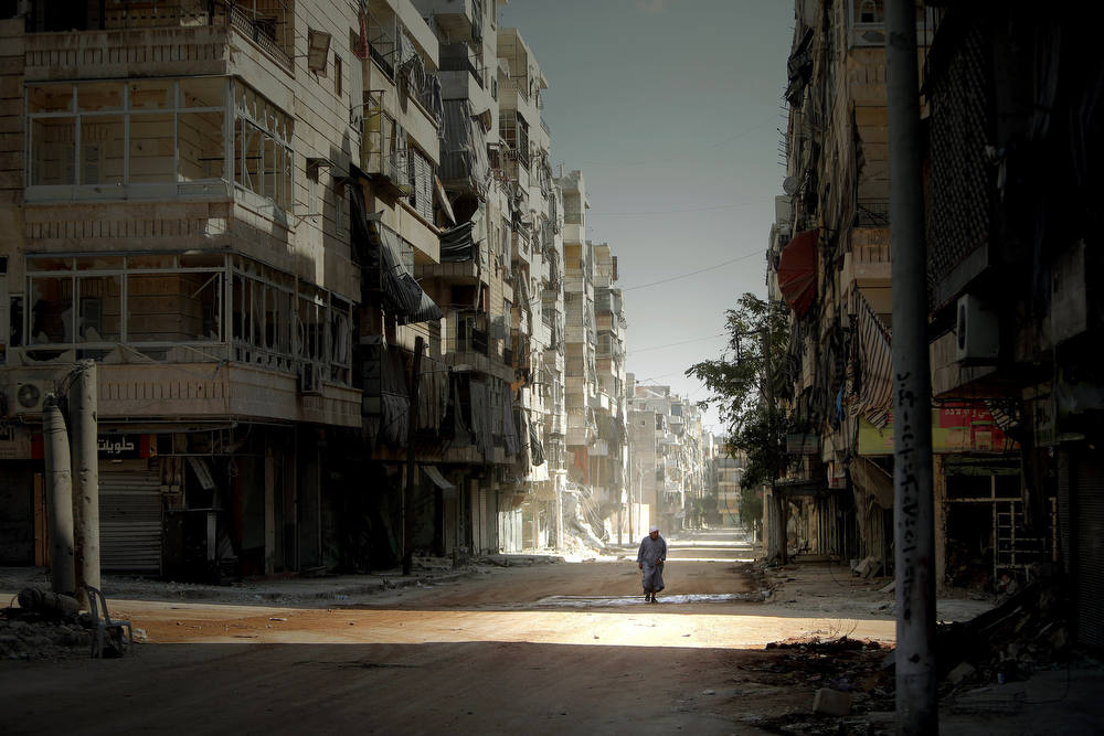 Description of . A Syrian man holds his robe while walking in the partially destroyed Salaheddin neighborhood of Aleppo, under the control of the Syrian army on September 3, 2012.  Syrian troops backed by artillery and warplanes fought rebels on multiple fronts on September 5 as peace envoy Lakhdar Brahimi described the death toll as