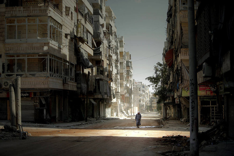 ". A Syrian man holds his robe while walking in the partially destroyed Salaheddin neighborhood of Aleppo, under the control of the Syrian army on September 3, 2012.  Syrian troops backed by artillery and warplanes fought rebels on multiple fronts on September 5 as peace envoy Lakhdar Brahimi described the death toll as ""staggering\"" and destruction \""catastrophic.\""  AFP PHOTO/JOSEPH  EID/AFP/Getty Images"