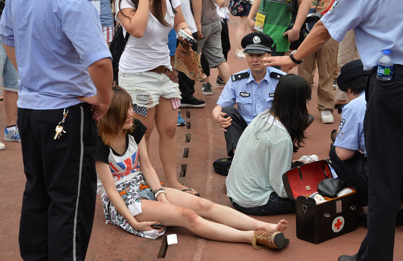 """. A woman is treated for injuries after being crushed in a stampede to see football superstar David Beckham at Tonji University in Shanghai on June 20, 2013. Beckham\'s visit to China turned \""""chaotic\"""" on June 20 after at least five people were hurt in a stampede as fans rushed to see him, local media and an AFP photographer at the scene said.  PETER PARKS/AFP/Getty Images"""