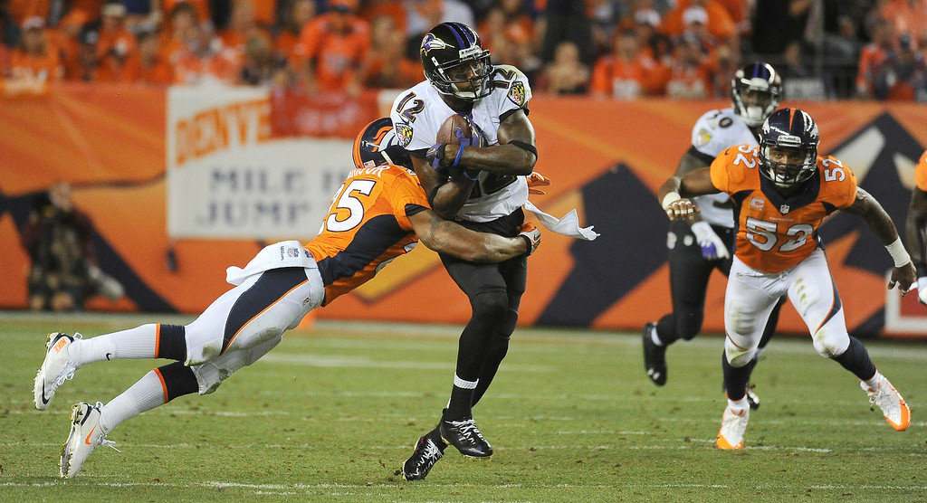 . Denver Broncos cornerback Chris Harris (25) tackles Baltimore Ravens wide receiver Jacoby Jones (12).  (Photo by Tim Rasmussen/The Denver Post)