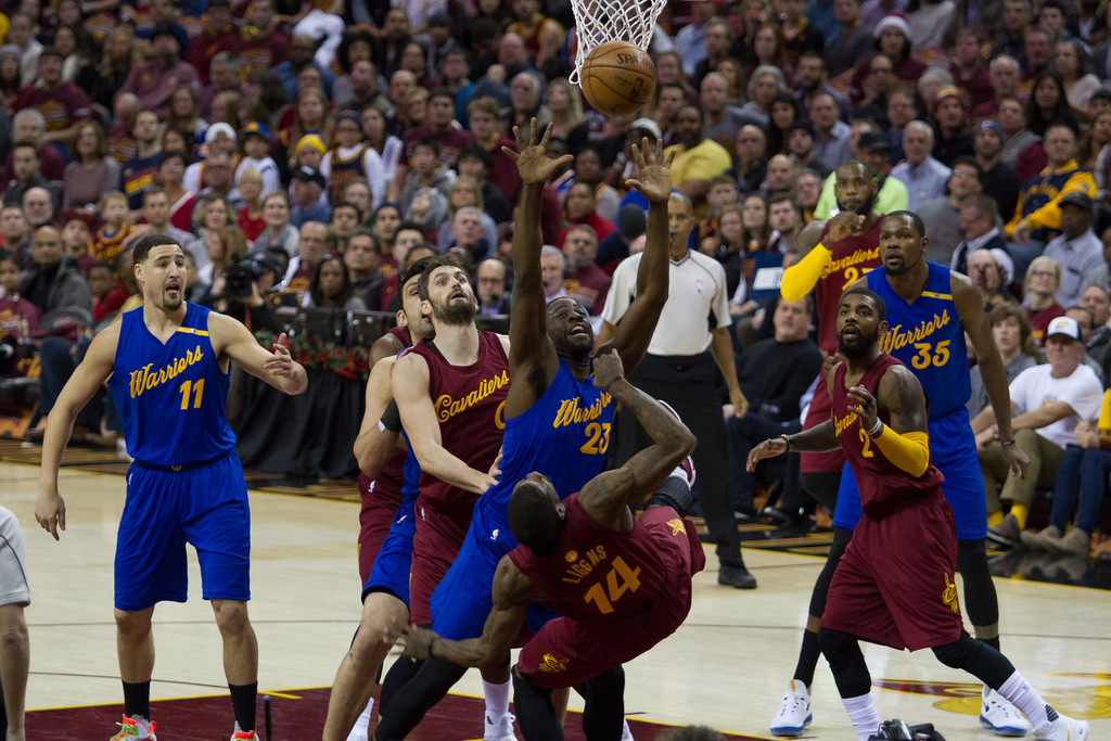 . Draymond Green (23) of the Golden State Warriors fouls the Cavaliers\' DeAndre Liggins (14) during an NBA game at the Quicken Loans Arena on Christmas day.  The Cavs defeated the Warriors 109-108.  Michael Johnson - The News Herald