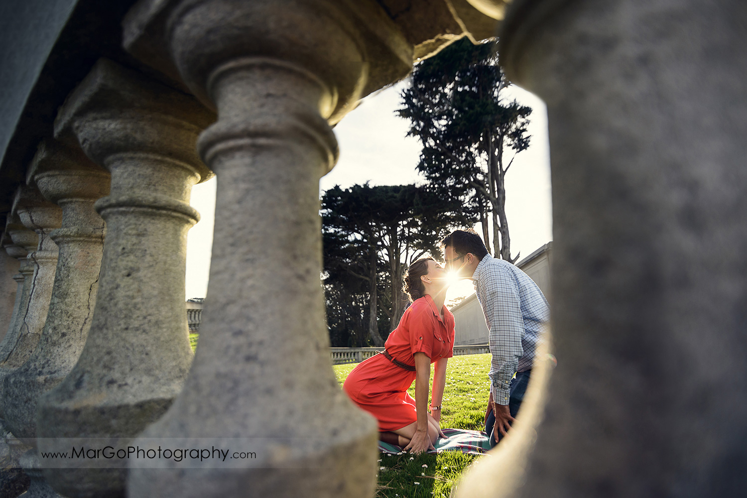 man in blue shirt and woman in red dress kissing during engagement session at San Francisco Legion of Honor shot through the columns