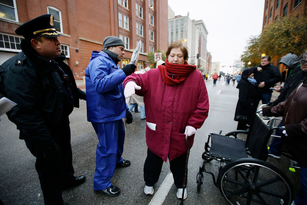 . Debbie Ford of McKinney, Texas goes through security before a ceremony to mark the 50th anniversary of the assassination of John F. Kennedy, Friday, Nov. 22, 2013, at Dealey Plaza in Dallas. President Kennedy\'s motorcade was passing through Dealey Plaza when shots rang out on Nov. 22, 1963. (AP Photo/Tony Gutierrez)