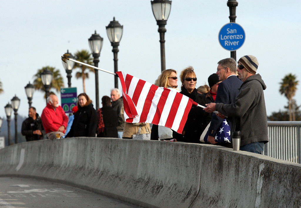 ". Hank Springer unfurls his flag on the Riverside Bridge in Santa Cruz, Calif., on Thursday, March 7, 2013, as he waits with other Santa Cruz residents for the funeral procession of slain Santa Cruz Police detectives Sgt. Loran ""Butch\"" Baker and Elizabeth Butler. (Dan Coyro/Santa Cruz Sentinel)"