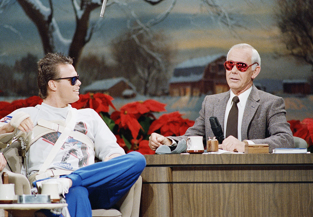 . Chicago Bears quarterback Jim McMahon, left, admires a pair of sunglasses worn by talk show host Johnny Carson during taping of The Tonight Show Starring Johnny Carson Wednesday night, Dec. 17, 1986, Burbank, Calif. McMahon was in California to have surgery, and gave Carson the sunglasses. McMahon was wearing a brace on his right shoulder to keep his shoulder immobile. (AP Photo/Mark Avery)