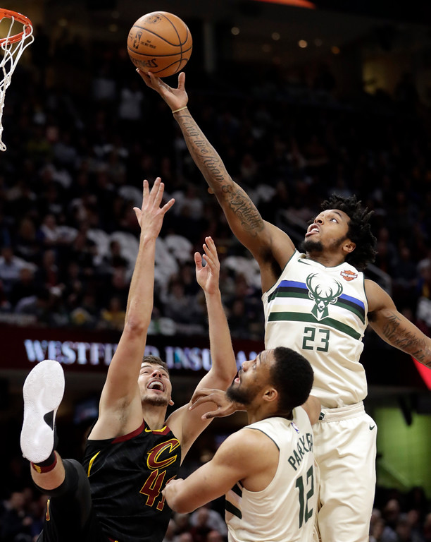 . Milwaukee Bucks\' Sterling Brown (23) and Jabari Parker (12) battle for a rebound against Cleveland Cavaliers\' Ante Zizic (41), from Croatia, in the first half of an NBA basketball game, Monday, March 19, 2018, in Cleveland. (AP Photo/Tony Dejak)