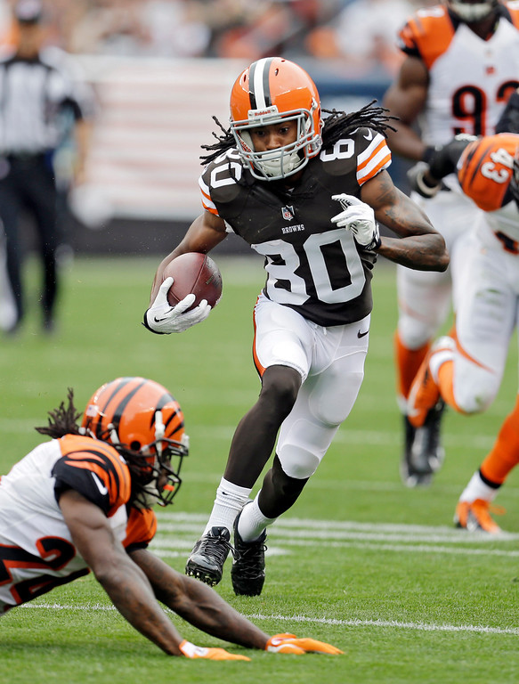 . Cleveland Browns wide receiver Travis Benjamin (80) avoids Cincinnati Bengals cornerback Adam Jones on a 39-yard pass reception in the first quarter of an NFL football game on Sunday, Sept. 29, 2013, in Cleveland. (AP Photo/Tony Dejak)