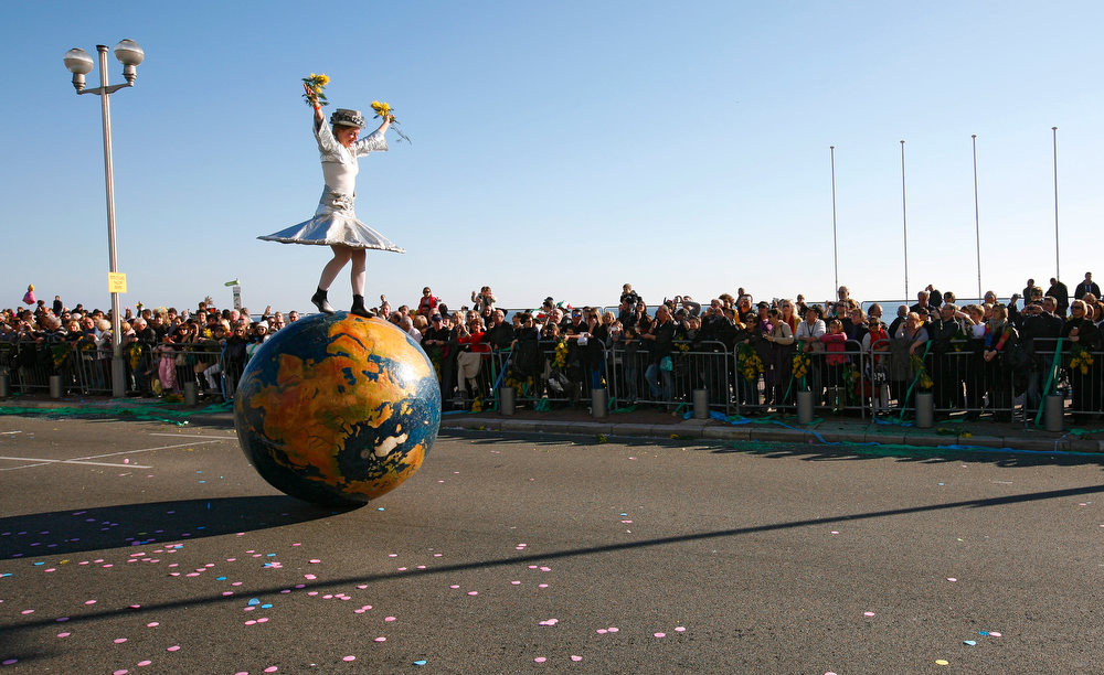 ". A reveler balancing on a globe parades during the flower parade of the 129th edition of the Nice Carnival, Saturday, Feb. 16, 2013, in Nice, southern France. The carnival celebrates the theme ""King of the 5 continents\"". (AP Photo/ Lionel Cironneau)"