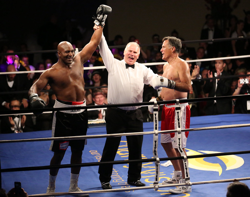 . Five-time heavyweight boxing champion Evander Holyfield, left, is declared the winner against Former Republican presidential candidate Mitt Romney during a charity fight night event Friday, May 15, 2015, in Salt Lake City. The black-tie event raised money for the Utah-based organization CharityVision, which helps doctors in developing countries perform surgeries to restore vision in people with curable blindness. (Kristin Murphy/Deseret News via AP)