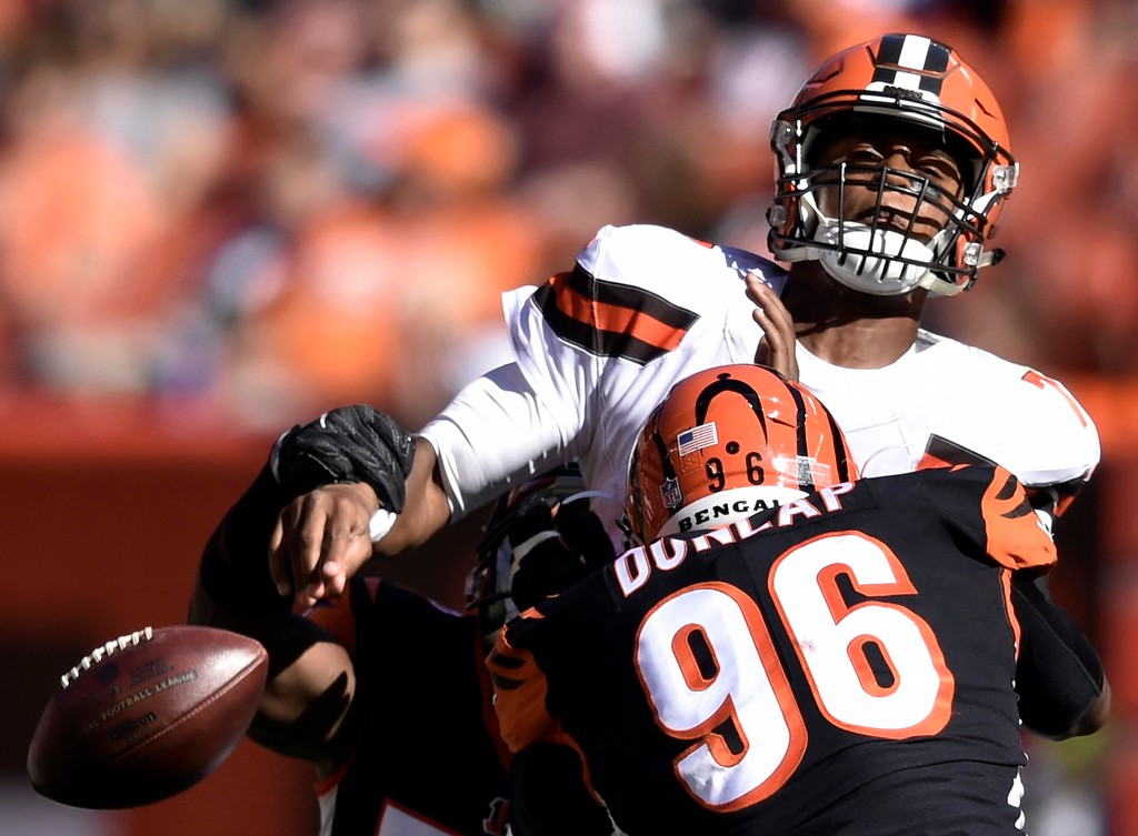 . Cleveland Browns quarterback DeShone Kizer, top, loses control of the ball under pressure from Cincinnati Bengals defensive end Carlos Dunlap (96) in the second half of an NFL football game, Sunday, Oct. 1, 2017, in Cleveland. (AP Photo/David Richard)