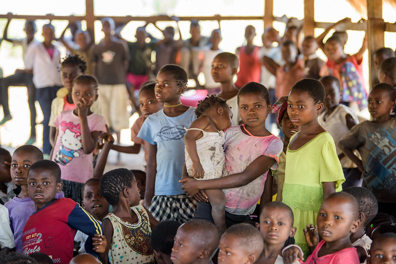 Children at the Child Friendly Space that Marie Ngalula, 14, and her siblings attend.  Marie lives with her father, Alexandre Tshimanga, her mother, Ntumba Kalombo Antoinette and her brothers and sisters: 1-Kena Tshimanga, 12 2-Kankonde Moise, 10 3-Munamba Angel, 8 4-Musungayi Andre, 6 5-Mubuyi Tshimanga, 4  Marie lives in a small village outside of Kananga, Democratic Republic of Congo, DRC, called Tubuluku, which means antelopes (plural). Her house is a two-room hut with a thatched roof.  Handful of wooden chairs are the only furniture. She lives here with an extended family of 13.  Home Life Marie is a bright girl but there is a sadness in her eyes. Marie's mother is in the nearby health clinic with a staph infection that has caused a huge abscess on her right side. It has become very serious. As a result, Marie has assumed many of the household duties.  She's forced, at 14, to assume the duties of an adult. Besides cooking for her brothers and sisters, she sweeps up the husks from palm nuts she crushes. She saves the husks to use as kindling for the fire. Marie and her siblings all sleep together in one room, huddled together for warmth and cover by an old and torn mosquito net.  Hunger Marie's family is desperately hungry in the days we visit them. Because her mother is sick and his father spends his days tending to her in the clinic, there is no money for food. Because there isn't any cassava flour and cornmeal to make fufu, a bread-like dish that's a Congolese staple, Marie and her siblings pick potato leaves from the garden. Marie sharpens a knife on a rock and uses it to chop the leaves into small pieces. She holds a bunch tightly in her left hand and runs the knife through them.  Her cousin, also named Marie Ngalula, pulls some wood from a pile and arranges it between three rocks that will hold the pot. She yanks some thatch from the roof and uses it for kindling. Because they also have no oil or salt, the recipe is uncomplicated.   The greens are stuck in