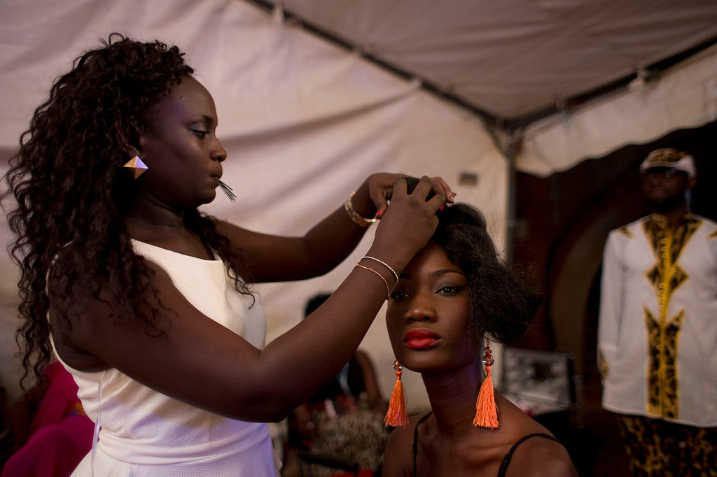 . A model gets her hair redone between designers, backstage at Hotel des Almadies, in Dakar, Senegal, Saturday, June 22, 2013. After a Friday show held in a dusty marketplace in the working class suburb of Guediawaye, the runway finale of Dakar Fashion Week was held at a luxury hotel and showcased the work of 14 designers from West Africa, Europe, South America, and the Caribbean. (AP Photo/Rebecca Blackwell)