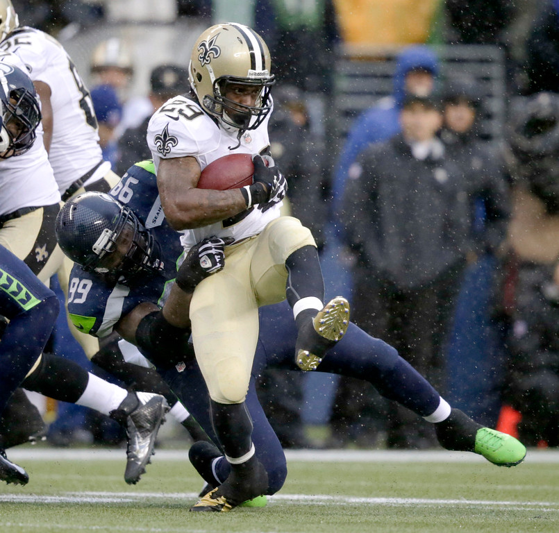 . New Orleans Saints running back Khiry Robinson, right, is tackled by Seattle Seahawks defensive tackle Tony McDaniel during the first half of an NFC divisional playoff NFL football game in Seattle, Saturday, Jan. 11, 2014. (AP Photo/John Froschauer)