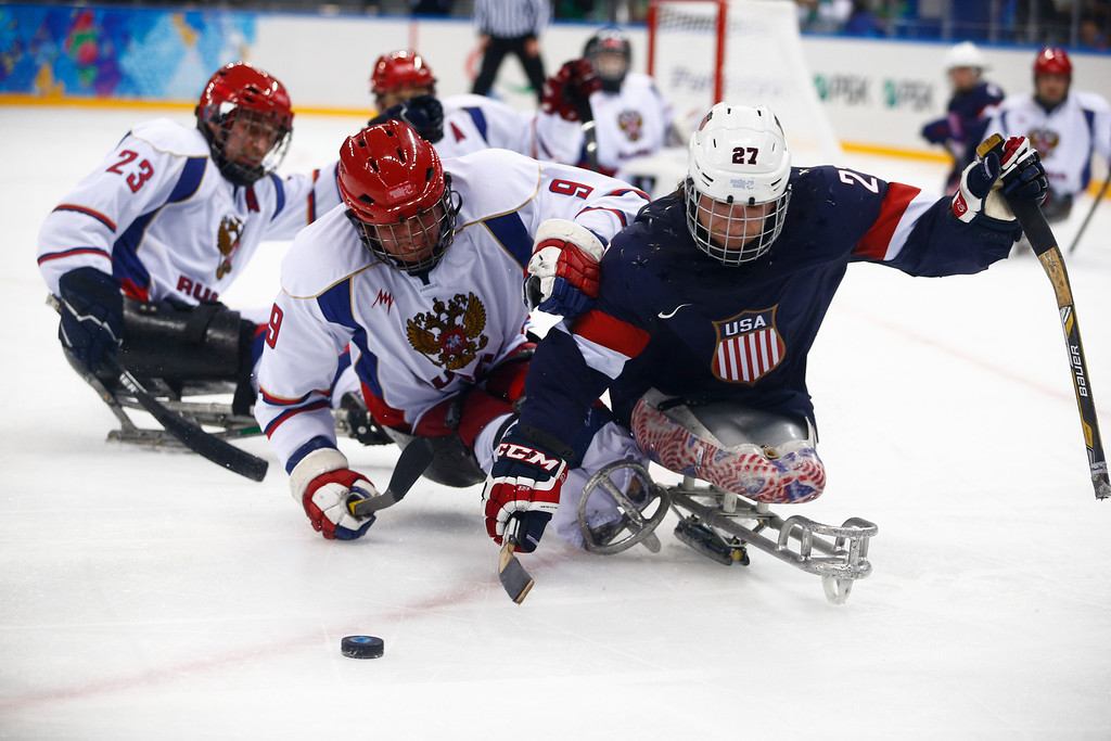 . United States\' Josua Pauls, right, in action with Russia\'s Konstantin Shikhov, center, and Ilia Volkov during an ice sledge hockey match between United States and Russia at the 2014 Winter Paralympics in Sochi, Russia, Tuesday, March 11, 2014. (AP Photo/Pavel Golovkin)