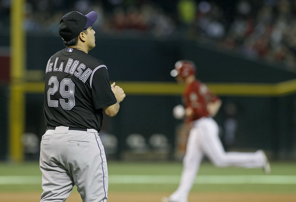 . Jorge De La Rosa #29 of the Colorado Rockies rubs up a new baseball as Nolan Reimold #12 of the Arizona Diamondbacks circles the bases following his two-run home run during the seventh inning of a MLB game at Chase Field on August 31, 2014 in Phoenix, Arizona.  (Photo by Ralph Freso/Getty Images)