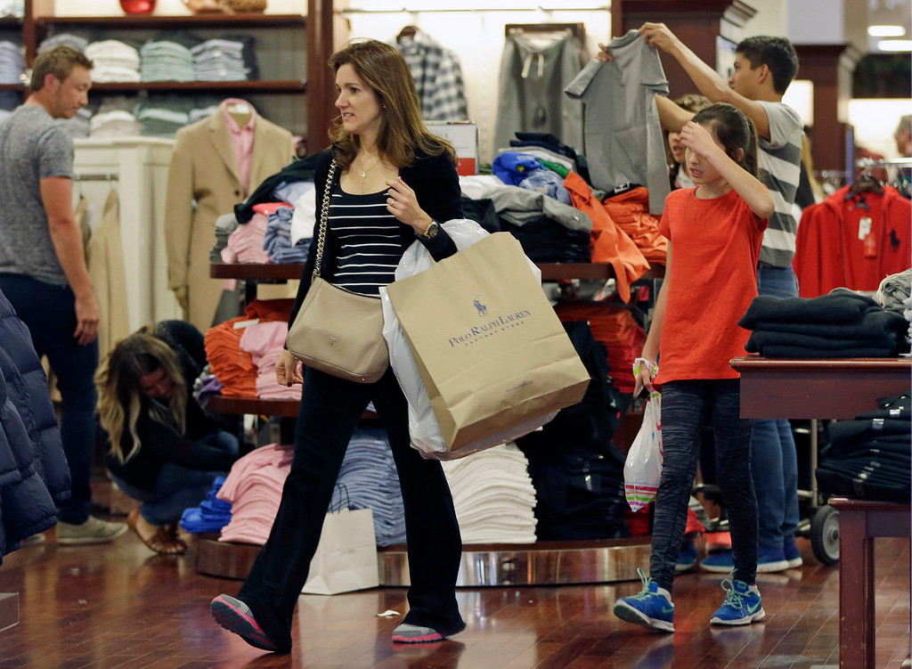 . A shopper carries a bag with merchandise as she shops at a Polo Ralph Lauren store on Black Friday, Nov. 25, 2016, in Miami. Stores open their doors Friday for what is still one of the busiest days of the year, even as the start of the holiday season edges ever earlier. (AP Photo/Alan Diaz)