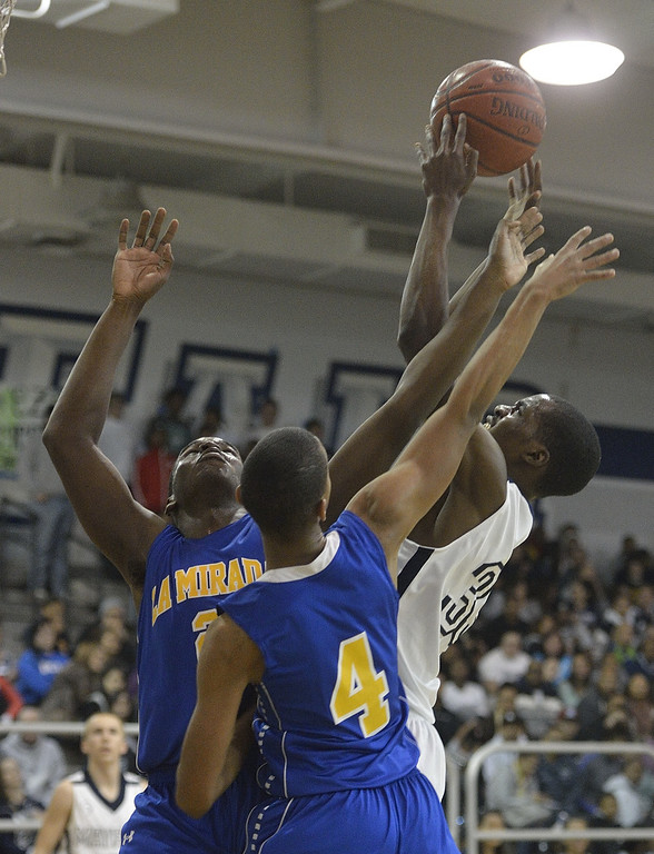 . LAKEWOOD, CALIF. USA -- Mayfair\'s Eze Egeonuigwe (33) and La Mirada\'s Jarrett Davis (2) and Khalil Stevenson (4) battle for a rebound in Lakewood, Calif., on February 8, 2013. Mayfair defeated La Mirada 60 to 59. Photo by Jeff Gritchen / Los Angeles Newspaper Group