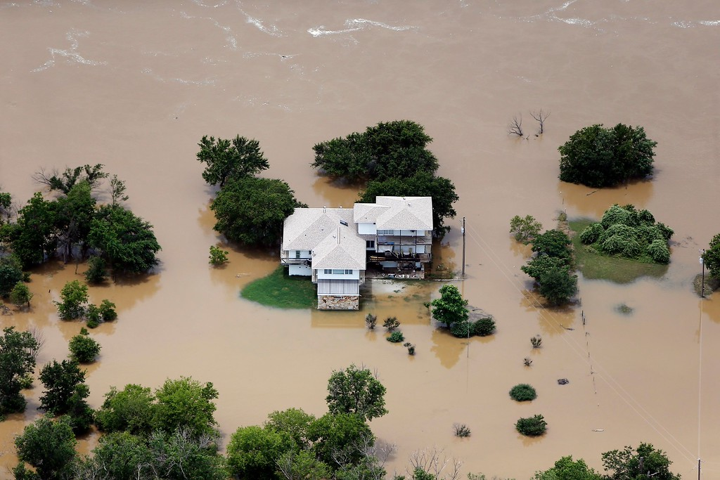 . Flood waters from the Brazos River encroach upon a home in the Horseshoe Bend neighborhood, Friday, May 29, 2015, in Weatherford, Texas. Floodwaters submerged Texas highways and threatened more homes Friday after another round of heavy rain added to the damage inflicted by storms. (AP Photo/Brandon Wade)